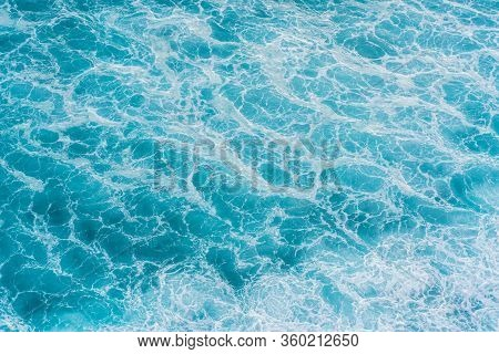 The Azure Surface Of The Ocean. Waves Break At The Shore. Texture Of The Water Surface Near The Shor