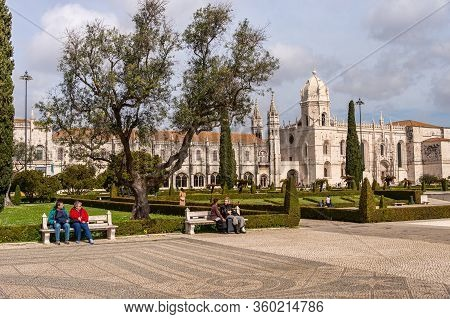 Lisbon, Portugal - 2 March 2020: People Sitting On Benches In A Park. Jeronimos Monastery In The Dis
