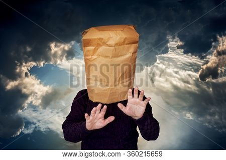 Man With A Package On His Head On A Stormy Sky Background. The Man Is Looking For A Blind Road