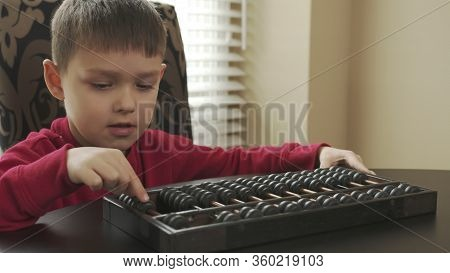 Little Schoolboy In A Red Sweater Siting At A Table And Learning Math On Old Abacus. Happy Child Tea