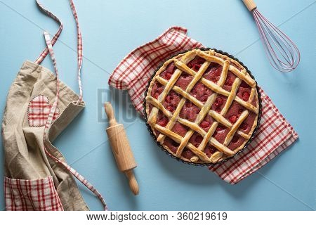 Raspberry Pie In An Oven Tray On A Blue Kitchen Counter. Baking Raspberry Pie Concept. Apron And Coo