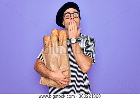 Young handsome baker man with blue eyes wearing french beret holding bag with bread cover mouth with hand shocked with shame for mistake, expression of fear, scared in silence, secret concept
