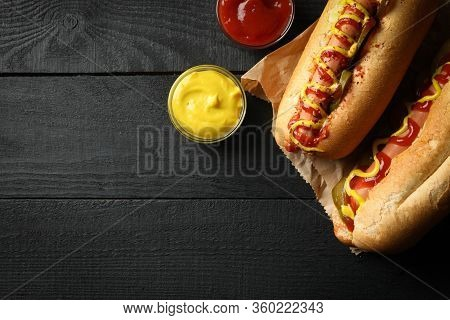 Tasty Hot Dogs And Sauces On Wooden Background