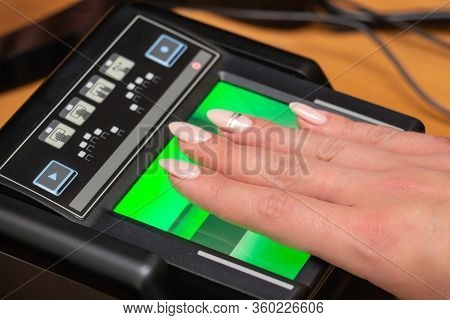 The Process Of Scanning Fingerprints During The Check At Border Crossing. Female Hand Puts Fingers T