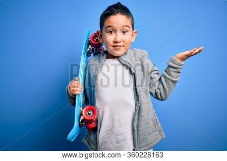 Young little boy kid skateboarder holding modern skateboard over blue isolated background very happy and excited, winner expression celebrating victory screaming with big smile and raised hands
