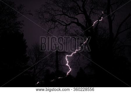 A Violent Lightning Strike At Night Behind Silhouetted Trees