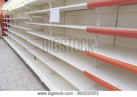 Empty Shelves In The Store. Supermarket With Empty Shelves For Goods. Concept: Sale And Demand For P