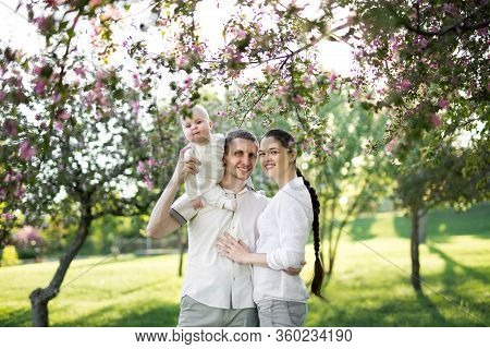 Portrait Of A Young Family With A Child. Happy Young Family Spending Time Outdoor On A Summer Day. H