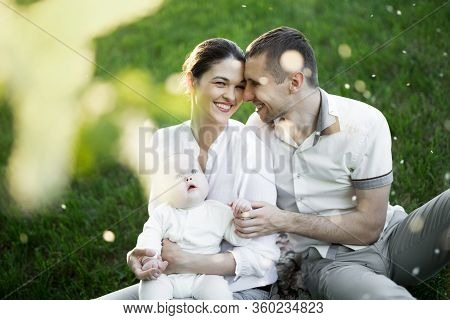 Portrait Beautiful Mother, Father And Baby Outdoors. Happy Family On A Summer Meadow.