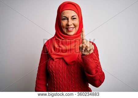 Middle age brunette woman wearing muslim traditional hijab over isolated white background pointing finger up with successful idea. Exited and happy. Number one.