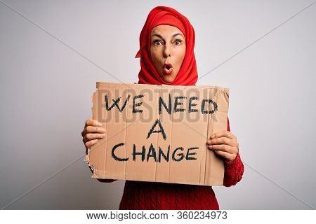 Middle age woman wearing muslim hijab asking for change holding banner scared in shock with a surprise face, afraid and excited with fear expression