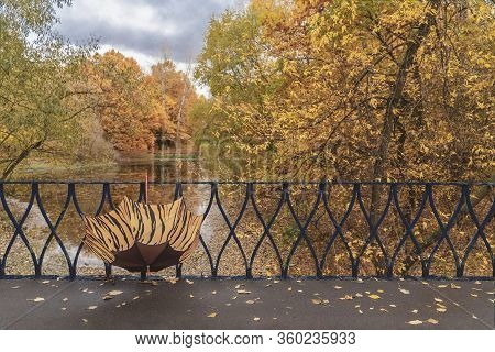 Vivid Open Bright Umbrella In Bridge Fence, Lattice By The Pond In The Old Park. Fall, Walking, Mood