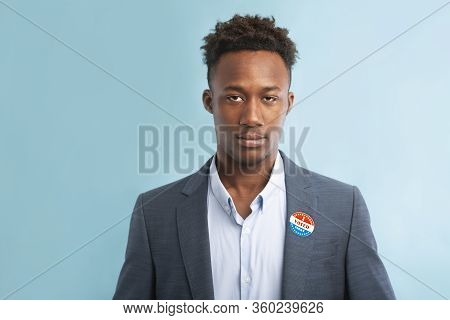 Elections In America 2020. African American Politician In Suit With Pinned Vote Button On Blue Backg
