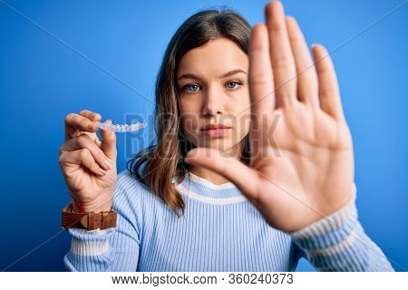 Young blonde girl holding dental orthodontic clear aligner over blue isolated background with open hand doing stop sign with serious and confident expression, defense gesture