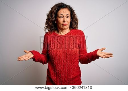 Middle age brunette woman wearing casual sweater standing over isolated white background clueless and confused with open arms, no idea concept.