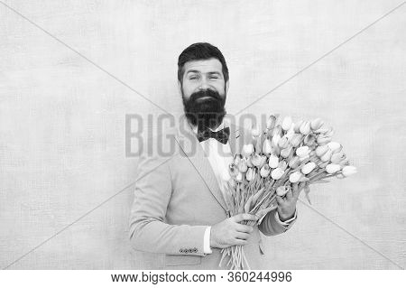 Spring Vibes. Man Bearded Suit Bow Tie Hold Tulip Flowers Bouquet. Gentleman Romantic Surprise For H