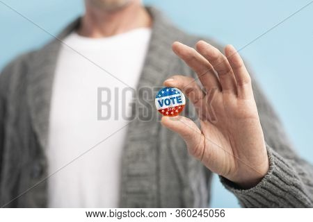 Vote 2020 In America, Us. Law Abiding American Citizen Holding Vote Pin In Hand, Blurred Background