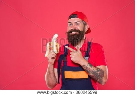 Is It Good Enough. Brutal Male In Cap And Uniform Eat Banana. Healthy Lunch Snack. Mature Man Builde