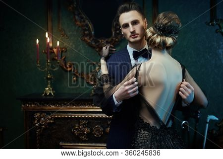 Glamorous couple of a man and a woman in the style of 1920s. Fashion clothes, make-up and hair in luxurious retro style.