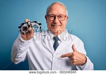 Senior grey haired optic doctor man holding optometrist eyeglasses over blue background with surprise face pointing finger to himself