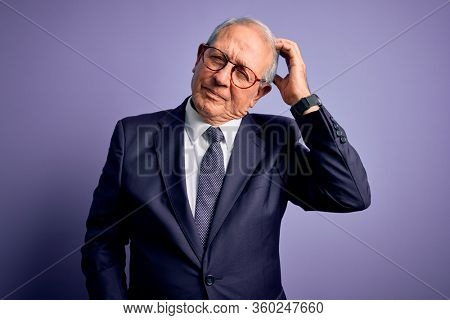 Grey haired senior business man wearing glasses and elegant suit and tie over purple background confuse and wondering about question. Uncertain with doubt, thinking with hand on head. Pensive concept.
