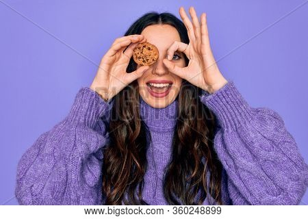 Young beautiful woman with blue eyes holding chocolate sweet coockie over eye with happy face smiling doing ok sign with hand on eye looking through fingers