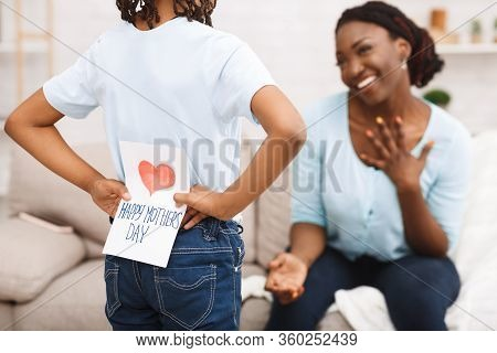 African Kid Hiding Greeting Card For Mom Behind Back, Congratulating Her On Mothers Day, Selective F