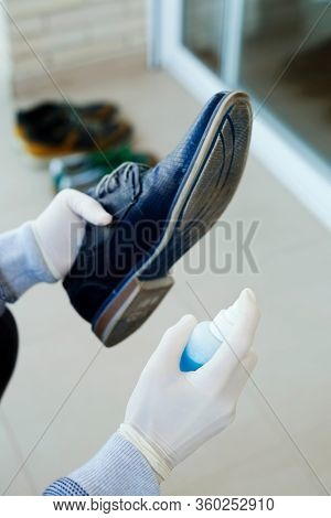 closeup of a man, wearing latex gloves, disinfecting the sole of his shoes by spraying a blue disinfectant from a bottle
