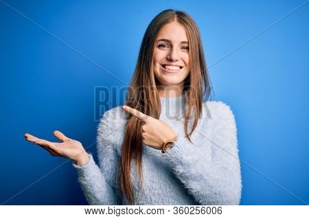 Young beautiful redhead woman wearing casual sweater over isolated blue background amazed and smiling to the camera while presenting with hand and pointing with finger.