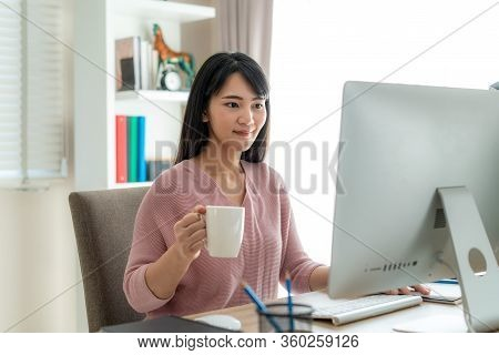 Asian Beautiful Young Woman Work From Home Working On Computer And Drinking Coffee While Working In