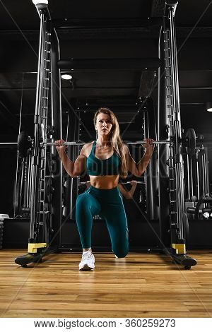 Sexy Sport Girl Doing Squat For Legs With Iron Barbell, Working Hard For Strong Muscles, Alone In Gy