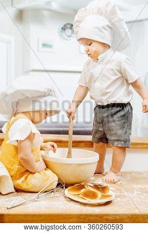 Charming Grimy Caucasian Children Cook Dough In White Cap