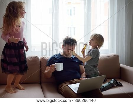 Tired Father With His Two Kids During Quarantine. Stay At Home Concept. Online Working And Household