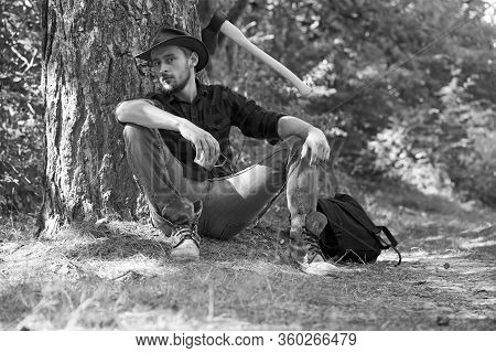 Lumberjack Worker Man Sitting In The Forest. Lumberjack With Axe On Forest Background. Man Doing Man