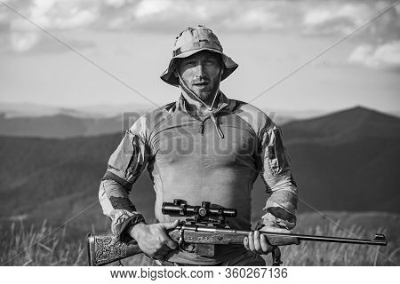 A Hunter With A Hunting Gun Hunt In Summer Forest. Mountain Hunting. Hunting Gear And Hunting Clothi