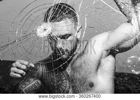 Destroy Obstacles. Fight Concept. Man Muscular Body Punching. Handsome Brutal Man Near Broken Glass.