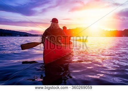 Couple Friends On A Wooden Canoe Are Paddling In Water During A Vibrant Sunny Sunset. Taken In India
