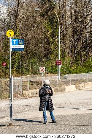 N. Vancouver - Apr 7, 2020: Woman Weaing Surgical Mask, Using Smartphone, While Waiting At Bus Stop