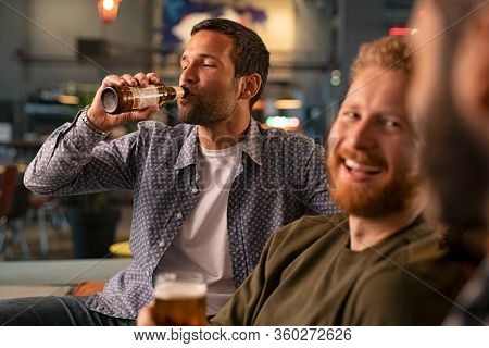 Mid adult friends having fun drinking cold beer sitting on couch at bar. Relaxed man drinking a bottle of beer in a pub while friends having conversation. Three happy young men talking.