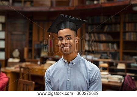 Happy african student in graduation cap standing in library and looking at camera. Portrait of a satisfied and proud graduate young man. Handsome african american student wearing mortar board.
