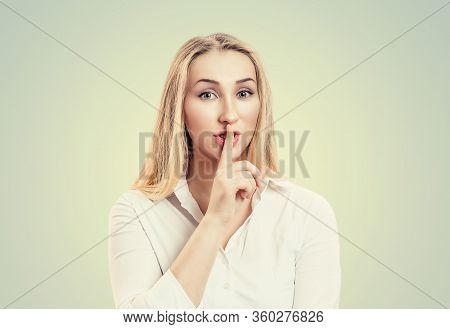 Woman Wide Eyed Asking For Silence Or Secrecy With Finger On Lips Hush Hand Gesture Green Background