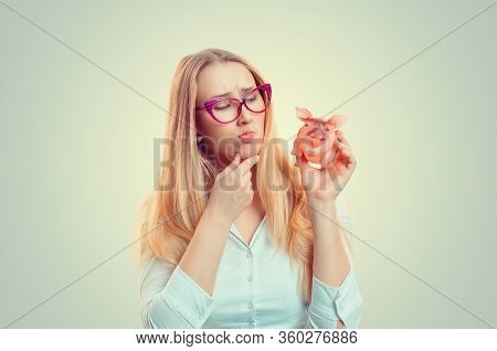 Closeup Portrait Stressed Young Woman Looking At Piggy Bank Thinking, Deciding Pondering Financial P