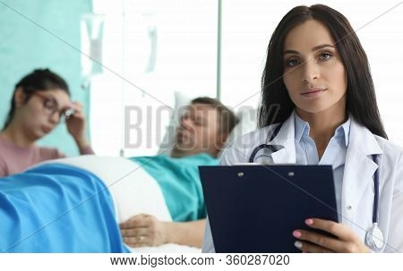 Doctor With Folder Is Standing In Palette Sick Man. Patient Are Monitored By Staff On Duty. Remote M