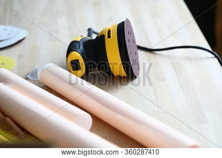 Close-up Of Bright Sander Machine Laying On Wooden Table. Papers With Plan Of Renovation. Working Pl
