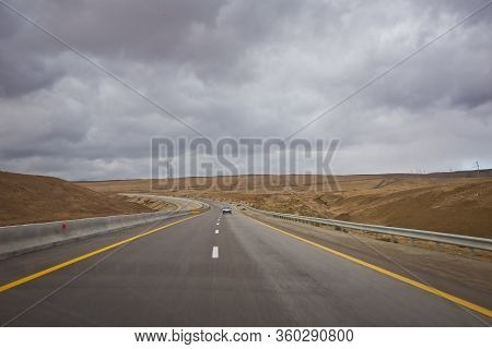 Asphalt Road And Bright Blue Sky With Fluffy Clouds . Empty Desert Asphalt Road From Low Angle With