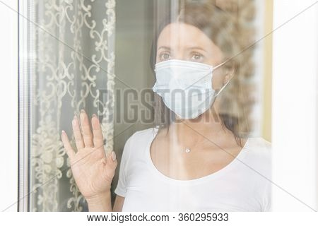 A Young Pretty Girl With A Sad Emotion. Coronavirus Self-quarantine. Sad Girl In Protective Mask Loo