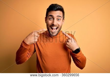 Young handsome man with beard wearing casual sweater standing over yellow background smiling cheerful showing and pointing with fingers teeth and mouth. Dental health concept.