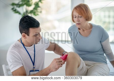 Smart Dark Haired Doctor Treating His Patients Limbs