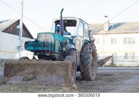 07/04/2020 Russia, Nigherodskaya Oblast, Poselok Svetlogorsk - An Old Turquoise Tractor Stands Near