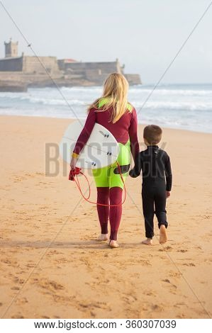 Back View Of Longhaired Mother And Son Walking On Beach. Woman With Surfboard Holding Hand Of Little